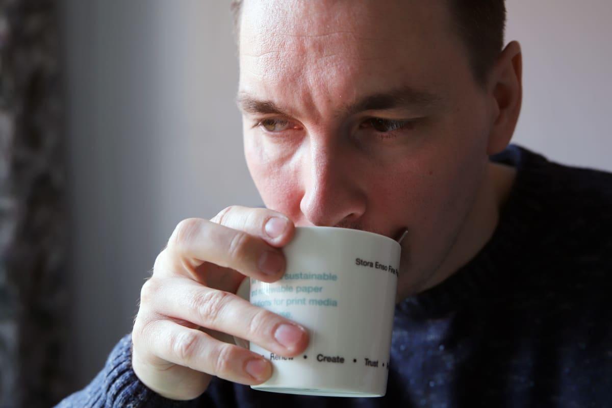 Mies juo kahvia valkoisesta kupista, jossa teksti Stora Enso Fine papers.