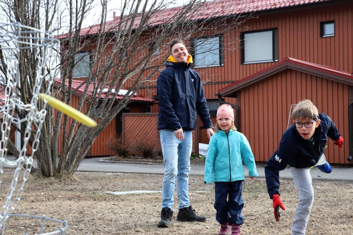Poika (Elmo Hyöppinen) heittää frisbeen koriin, vieressä sisko Mila ja isä Kimmo Hyöppinen.