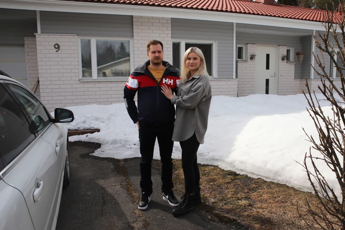 Mies ja nainen, Tero Lehtisalo ja Tia-Maria Korhonen, seisovat rinnakkain omakotitalon edessä. Pihalla lunta.