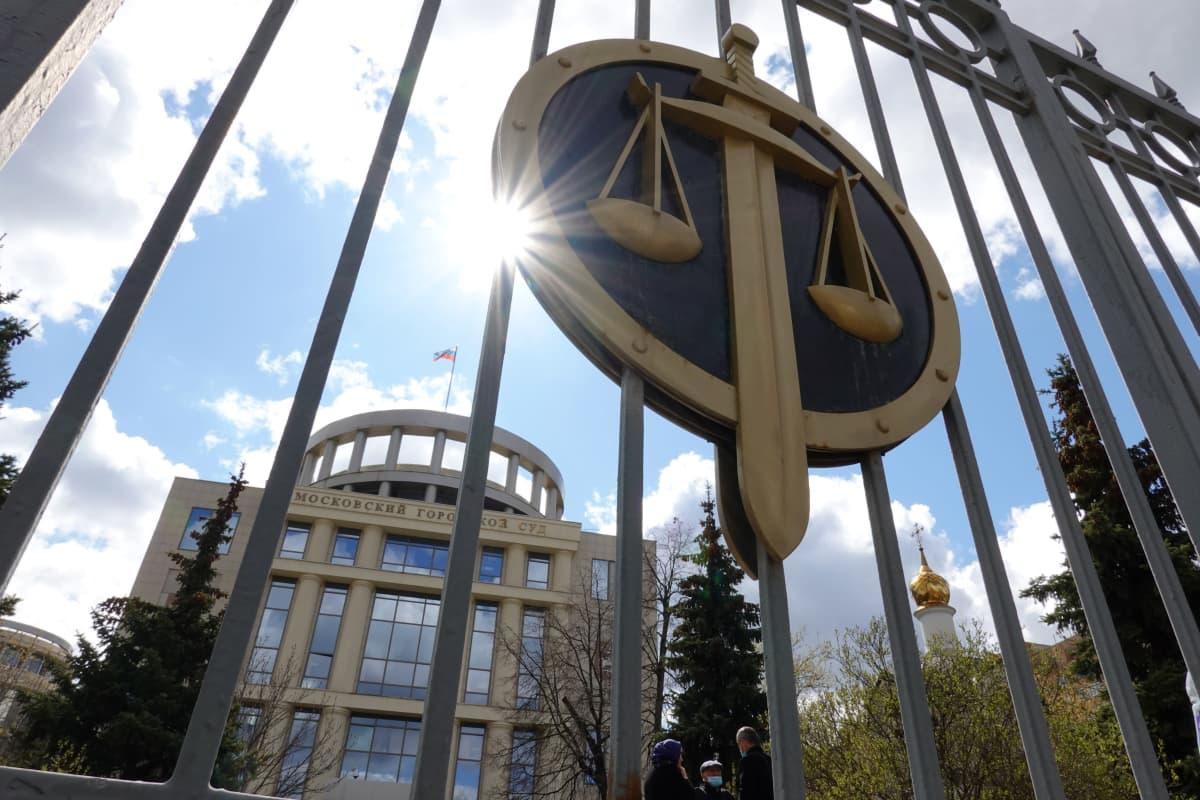 Tuomioistuimen porttia koristaa miekan ja vaa'an symboli. Portin läpi näkyy tuomioistuimen rakennus..