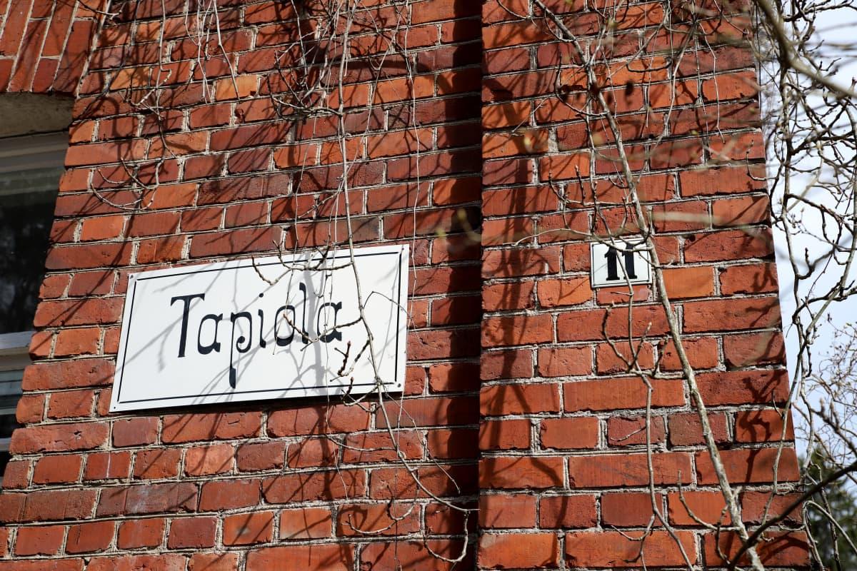 Vanhan tiilitalon kyljessä talon nimikyltti jossa lukee Tapiola