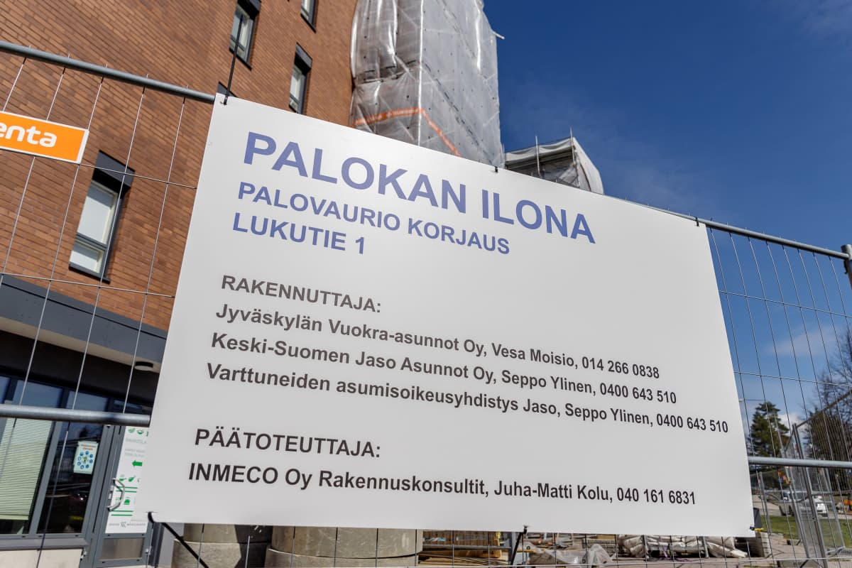 Kyltissä lukee Palokan Ilona, Palovaurion korjaus. Taustalla huputettu kerrostalo.
