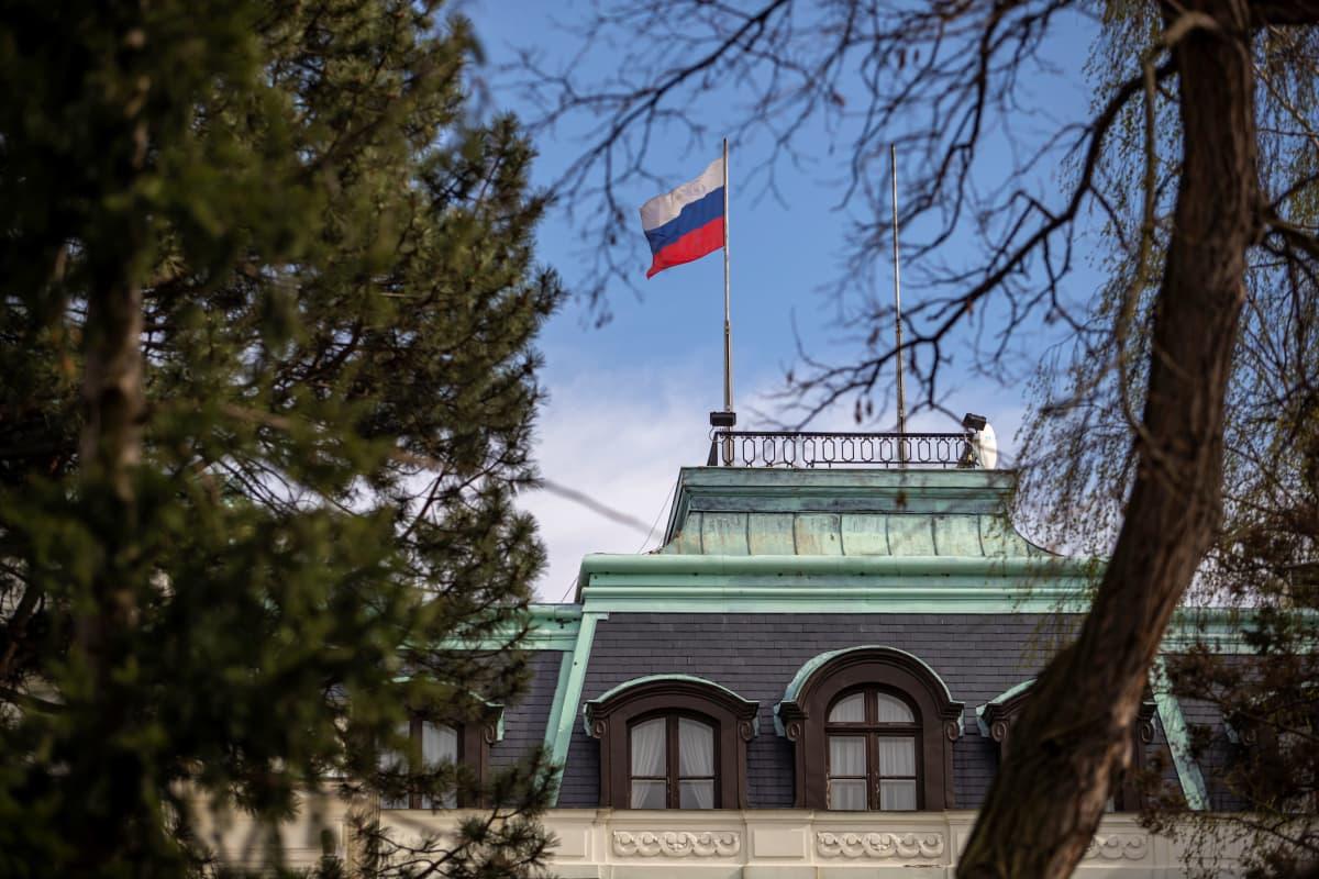 Venäjän lippu liehuu lähetystörakennuksen katolla. Kuvaa reunustavat puut.