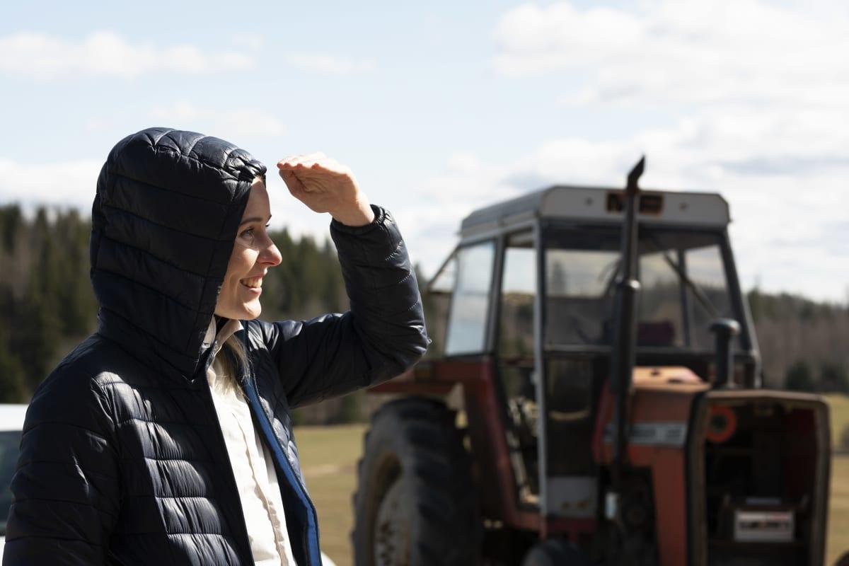 Kristiina Mäkelä står ute på landsbygden framför en traktor.