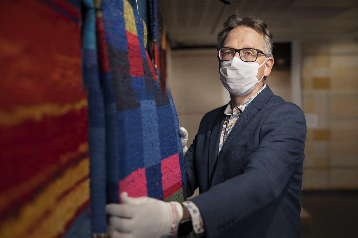 Suomen käsityön museon intendentti Mikko Oikari kokeilee Rasinmäen mattoa valkoiset käsineet kädessään.