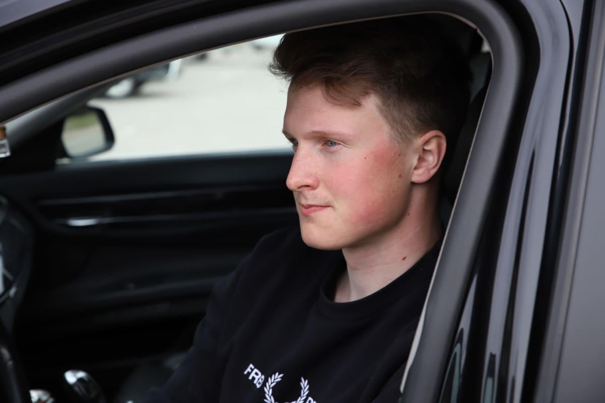 Kärköläläinen Onni-Kalle Lahdelma istuu autossa.
