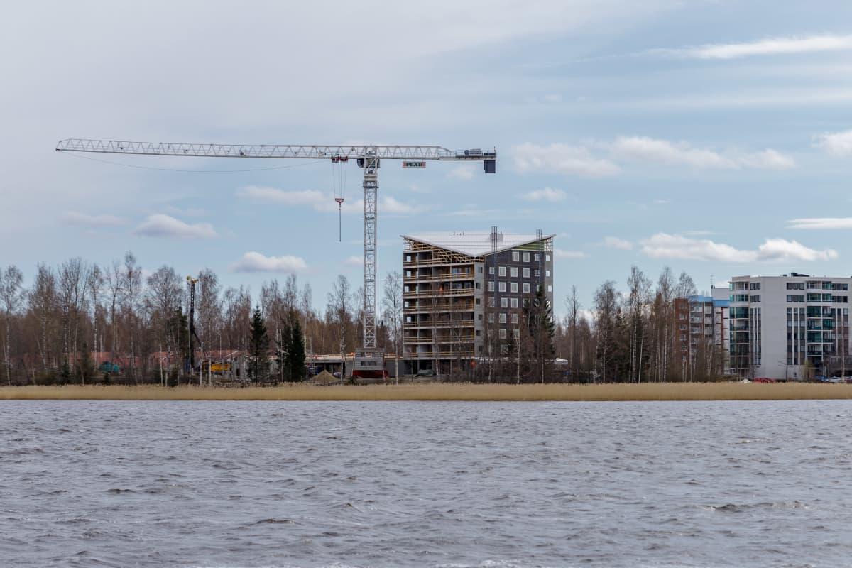 Järven takana nosturi ja rakennusvaiheessa oleva kerrostalo.