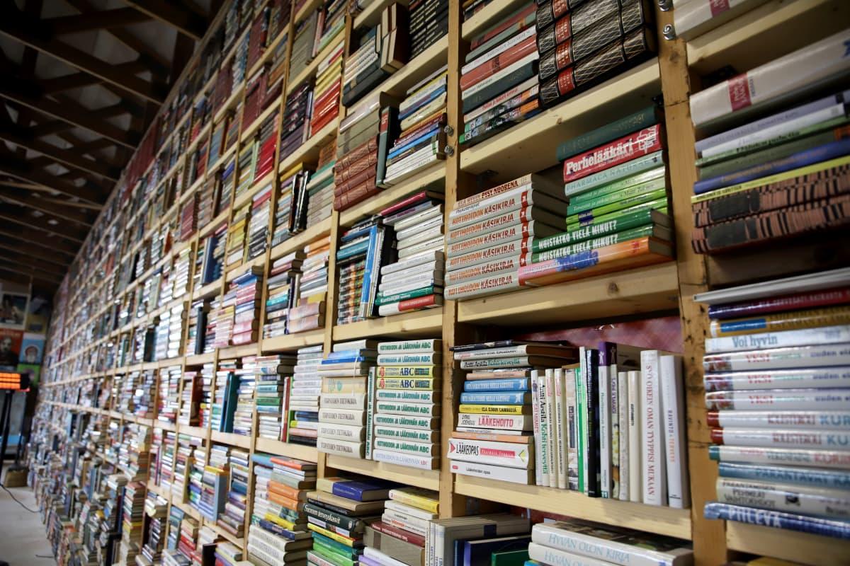 Hallissa koko seinän levyinen ja korkuinen hylly täynnä vanhoja kirjoja