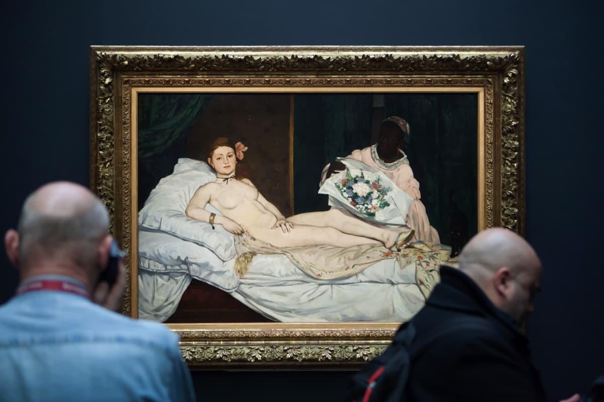Vierailijoita museossa taulun edessä, jossa renessanssityyliin maalattuna alaston aatelisnainen makaamassa sängyllä.