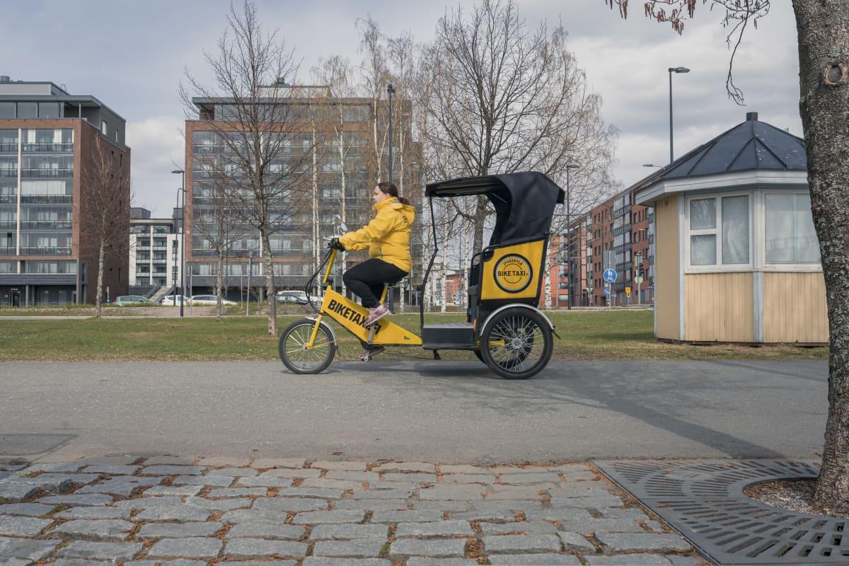 Biketaxi Jyväskylän yrittäjä Anne Muukkonen ajaa riksataksia.