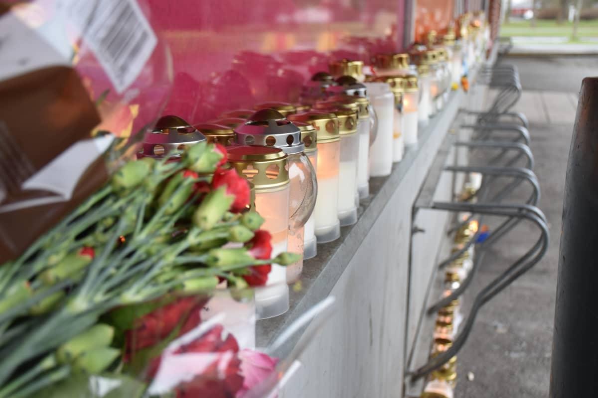 Kynttilämeri ja kukkasia kauppakeskuksen edessä.