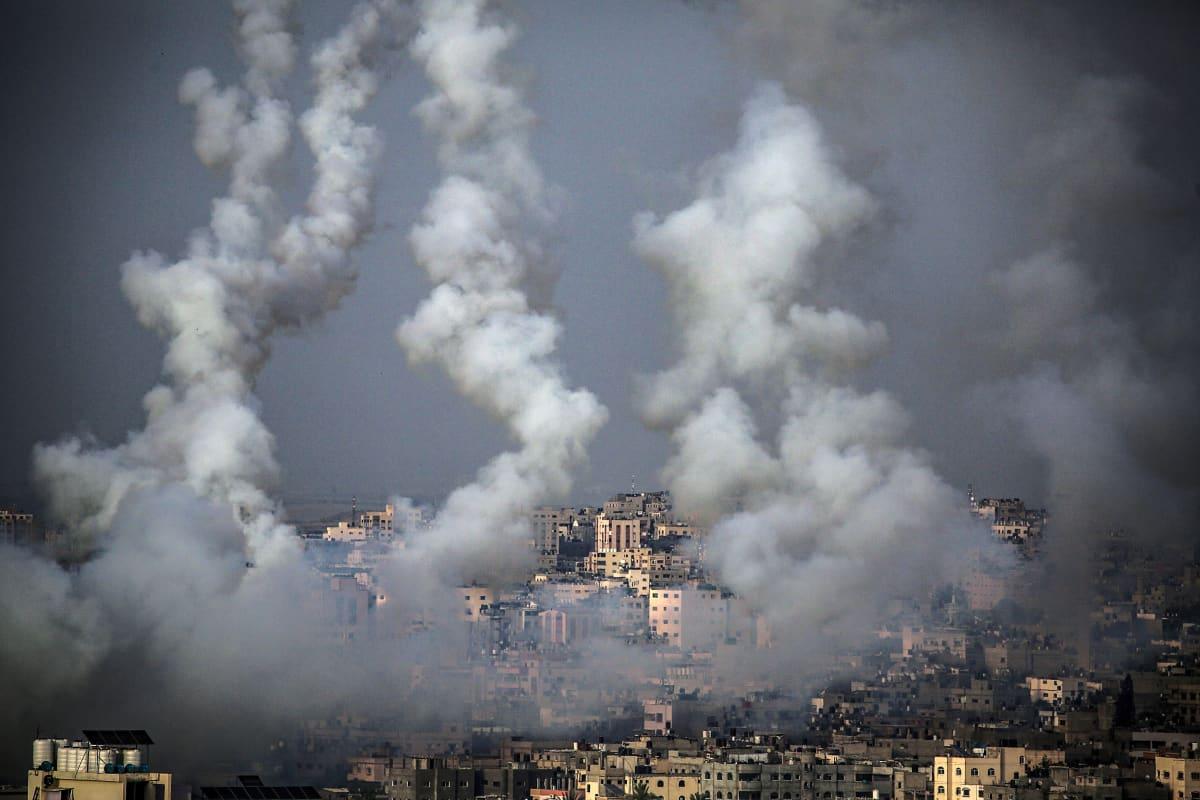 Gazasta lähteneet rakettien savuvanat taivaalla kaupungin yläpuolella.