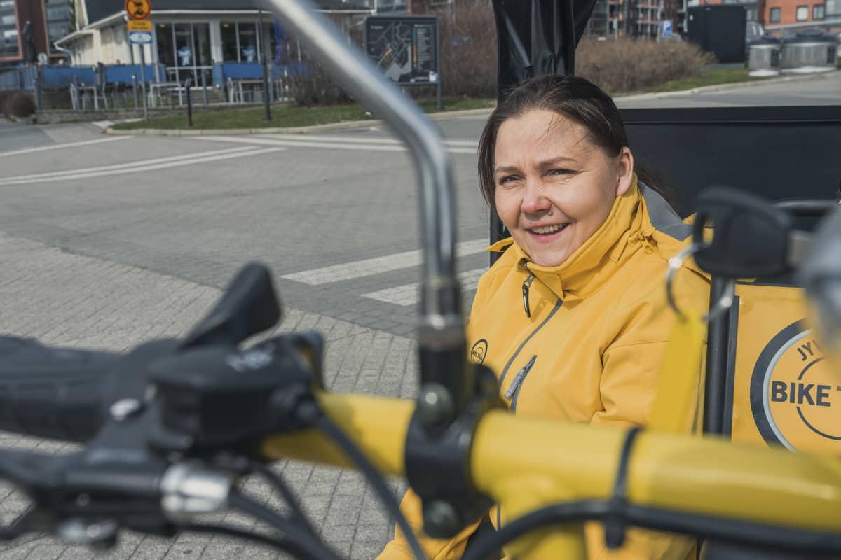 Biketaxi Jyväskylän yrittäjä Anne Muukkonen istuu riksataksin sivussa Jyväskylän satamassa.