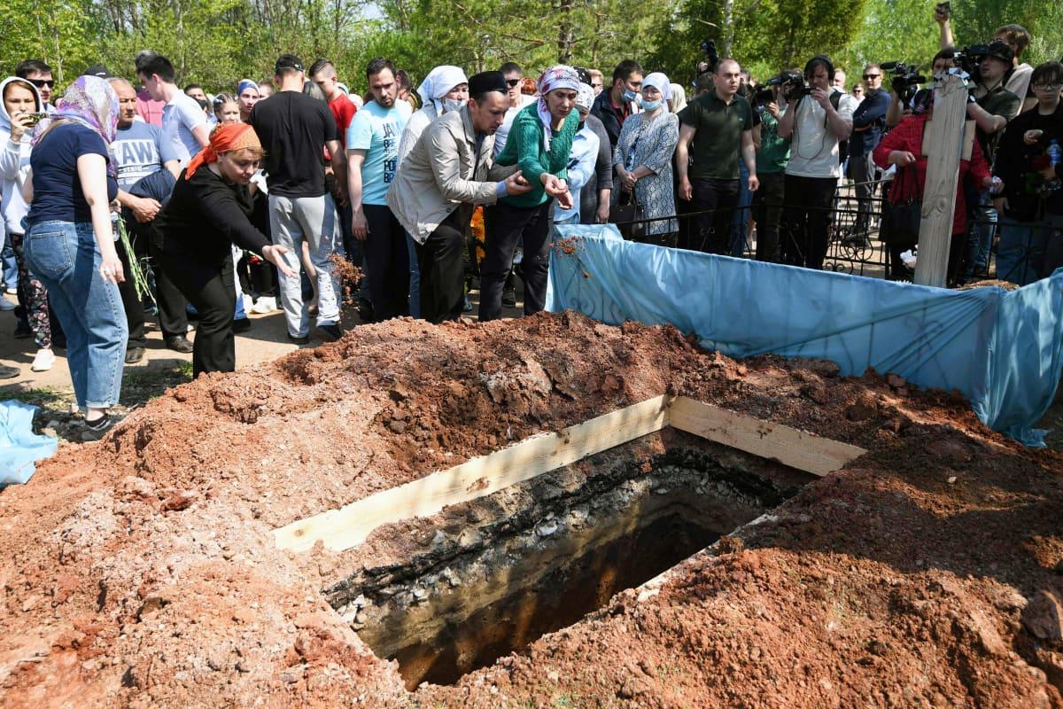 Hautajaisvieraat heittäväät hiekkaa avonaiseen hautaan.