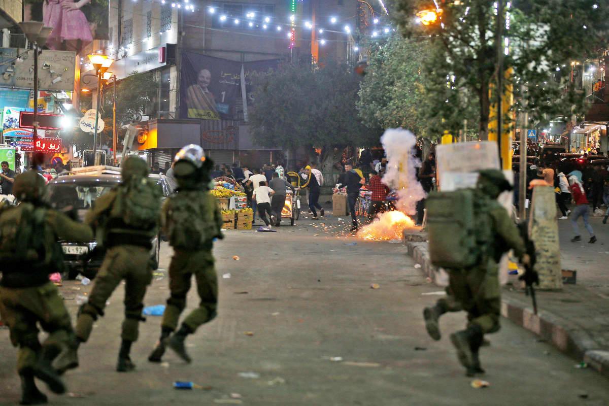 Palestiinalaisia ja Israelin armeijan turvallisuusjoukkojen sotilaita kadulla Hebronissa.