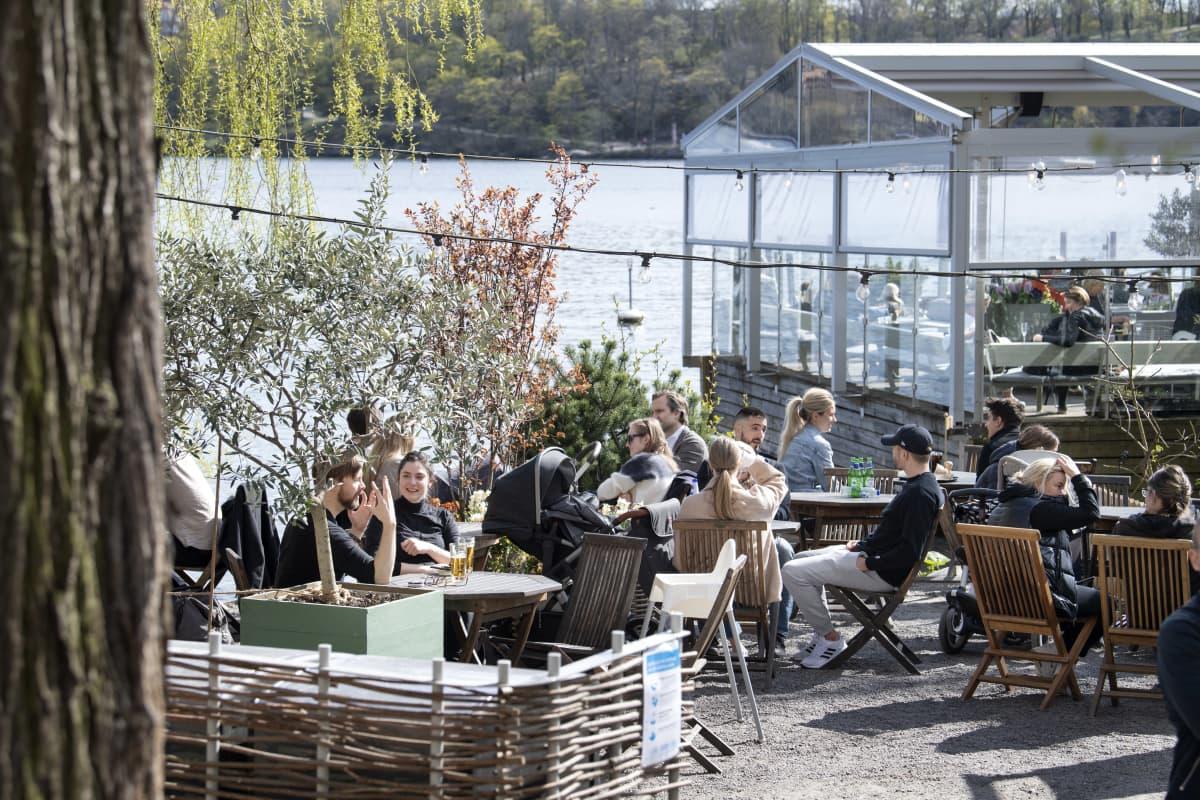 Ihmisiä terasseilla nauttimassa ulkoilmasta Tukholmassa.