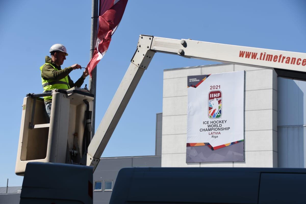 Rakennusmies asentaa Latvian lippua lipputankoon.