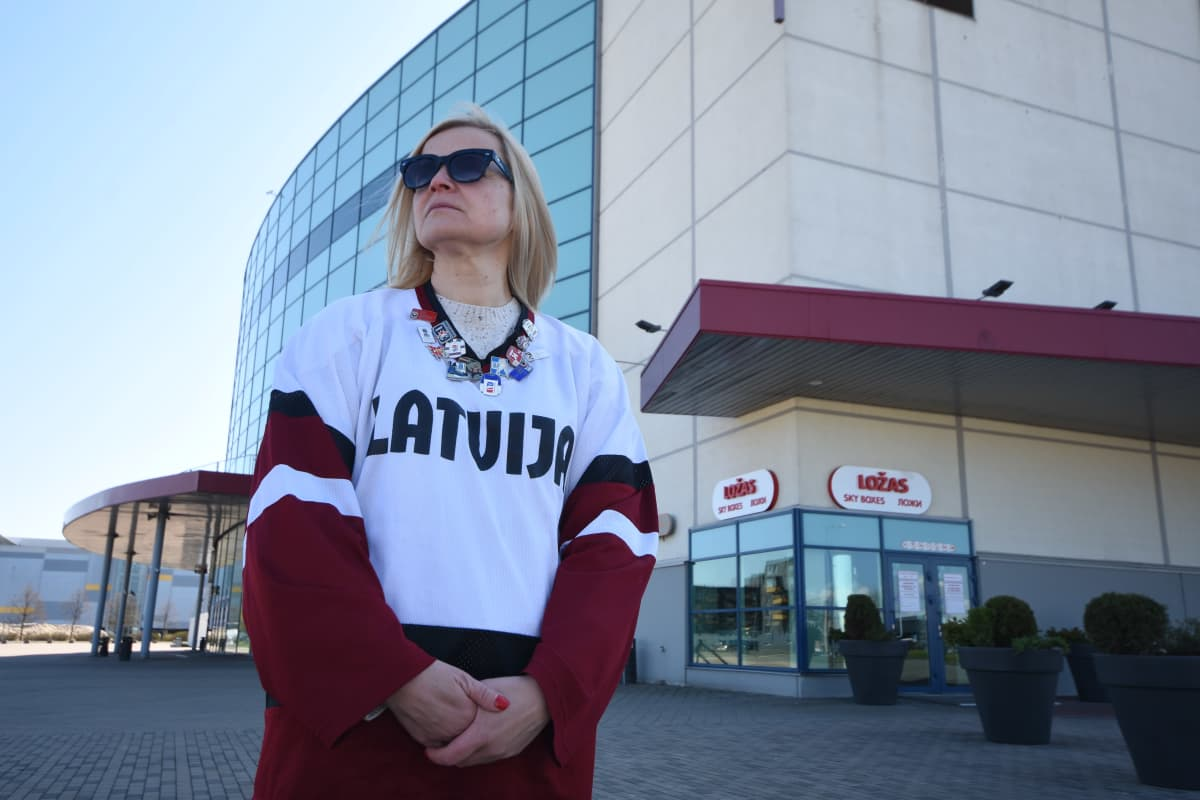Latvialainen kiekkofani Dace Kokle poseeraa Arena Riga -jäähallin edessä.