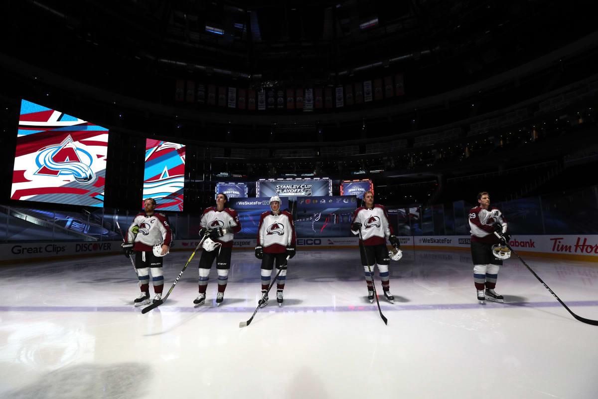 Colorado Avalancen pelaajat Gabriel Landeskog, Ryan Graves, Cale Makar, Mikko Rantanen ja Nathan MacKinnon seisovat rivissä keskellä kenttää