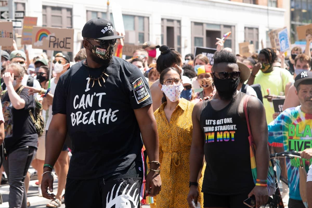 Kaksi mustaihoista miestä, joiden paidoissa on iskulauseita.