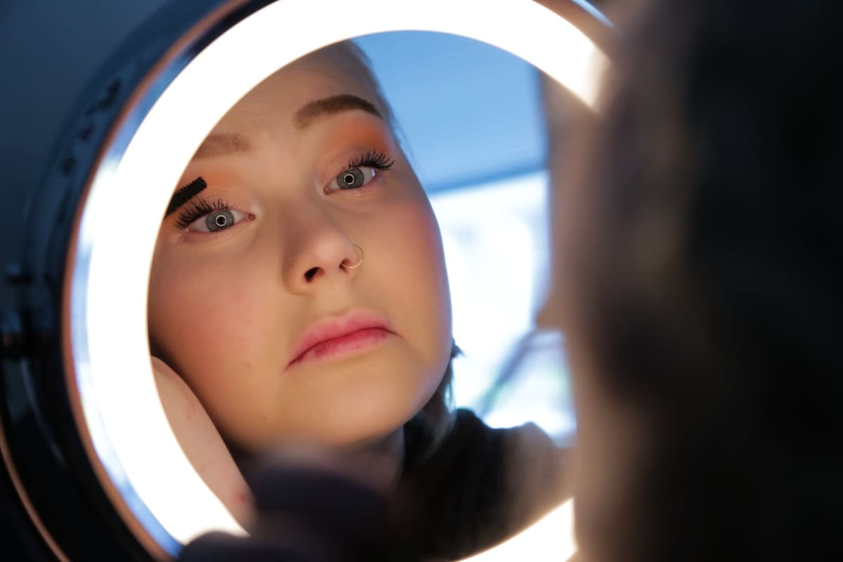 Vilma Parkkonen meikkaa peilin edessä.