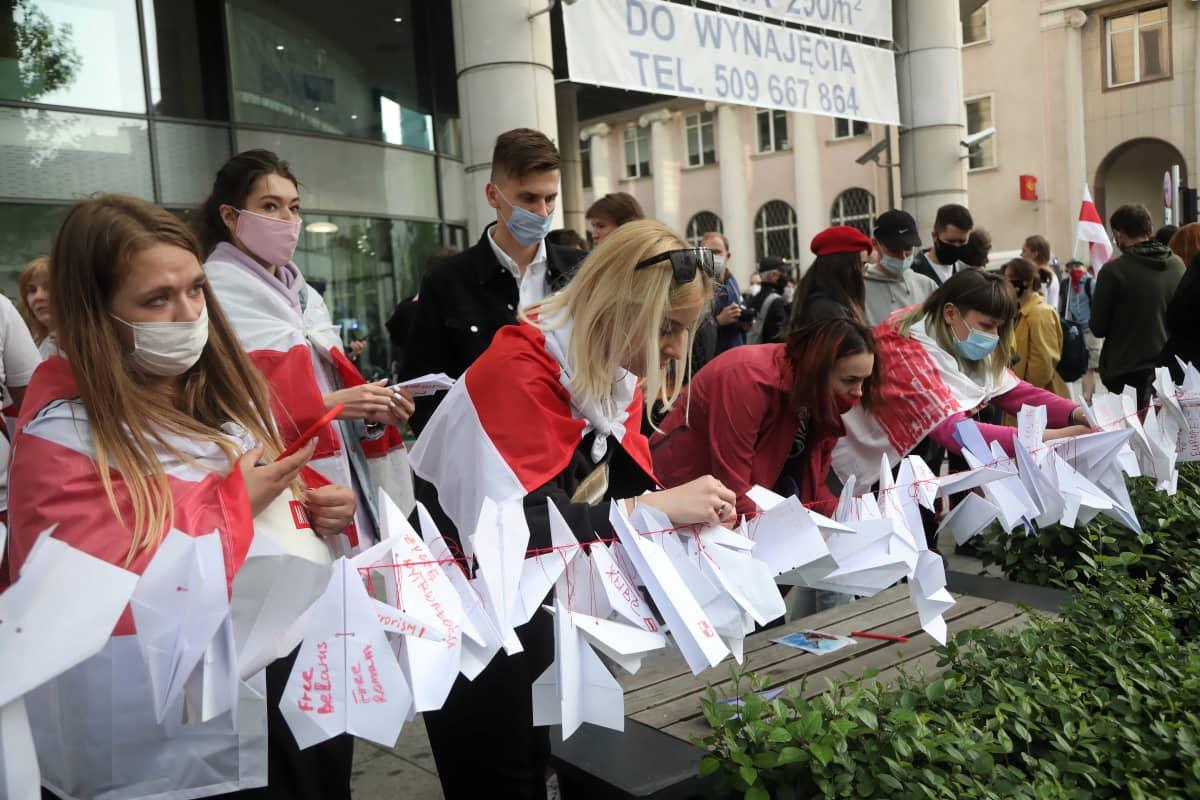 Lippuihin kääriytyneet mielenosoittajat kiinnittävät paperilennokkeja naruun.