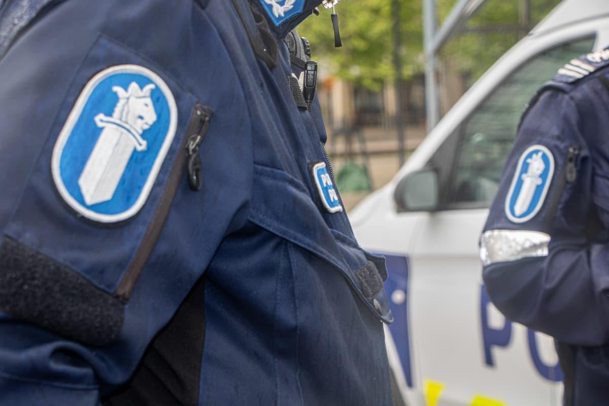 Kaksi poliisia tunnitamattomassa lähikuvassa. Poliisin hihamerkit näkyvillä.