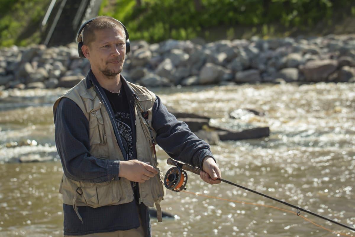Mies kalastaa Tikkurilankoskella.