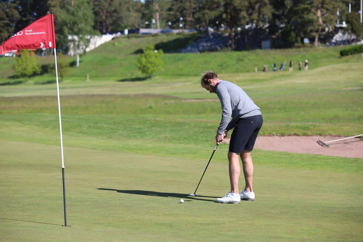 Mies puttaa golfpalloa