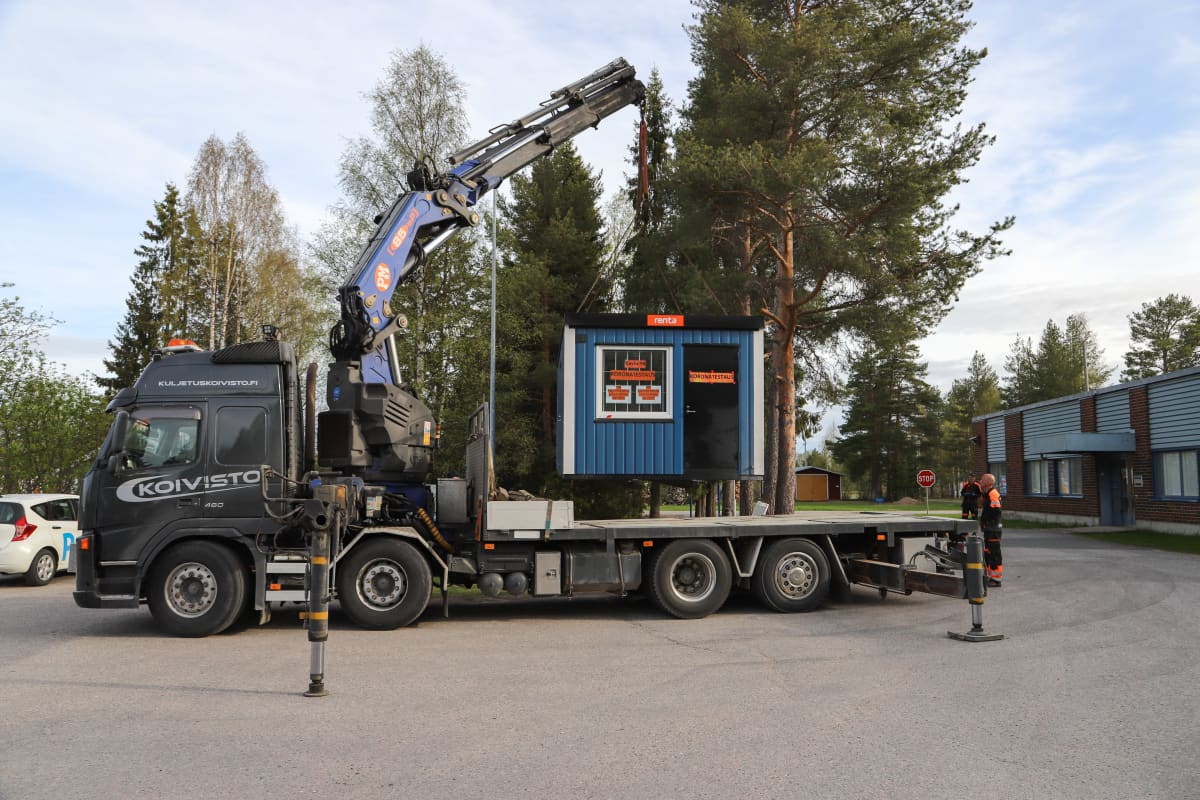 Koronatestikonttia siirretään kuorma-auton lavalle Pellossa. Testikontti siirtyy terveyskeskukselta Ruotsin rajalle.