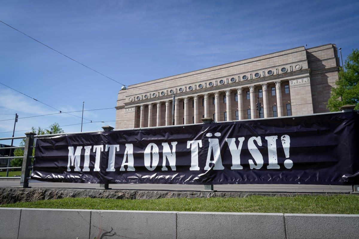 """Kulttuurialan mielenilmaus Eduskuntatalon ja Oodin välissä. Kuvassa banderolli jossa lukee """"mitta on täysi""""."""