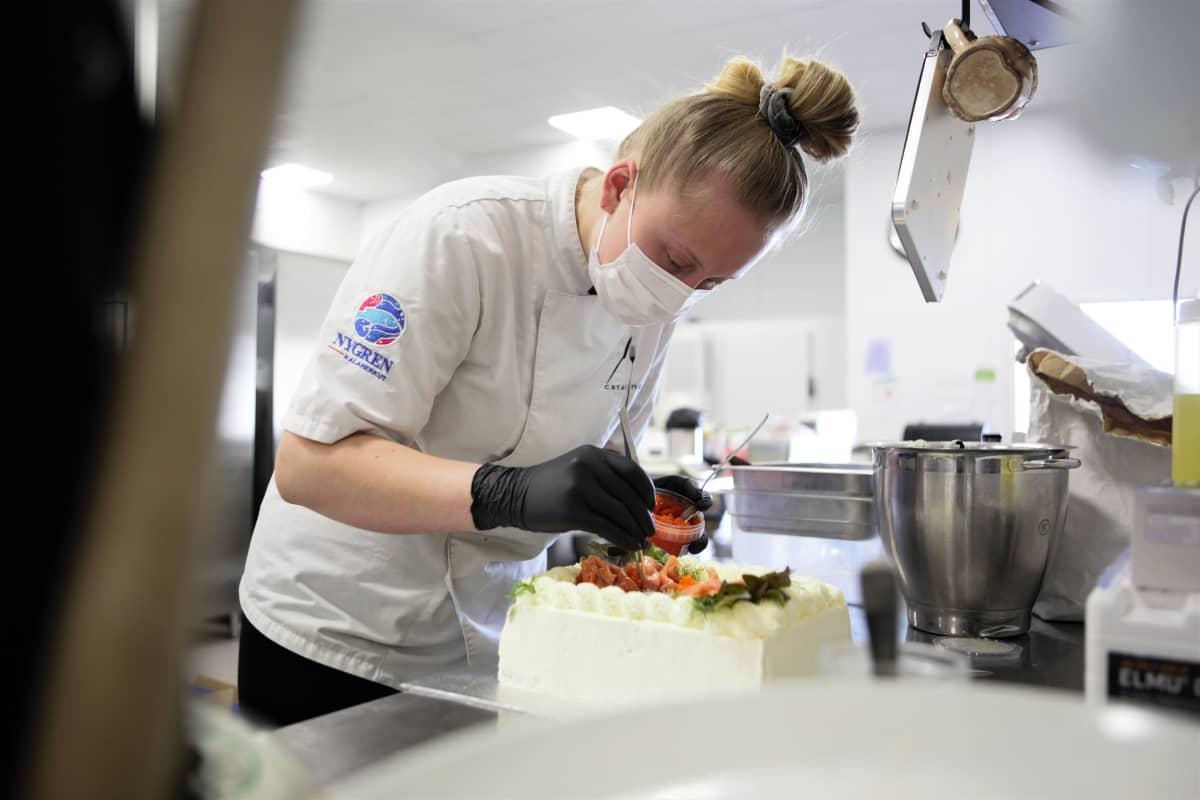 Mira Hanski viimeistelee voileipäkakkua valmistujaisviikonlopun edellä 4catering-pitopalvelun tiloissa Linnakallion teollisuusalueella Pirkkalassa.