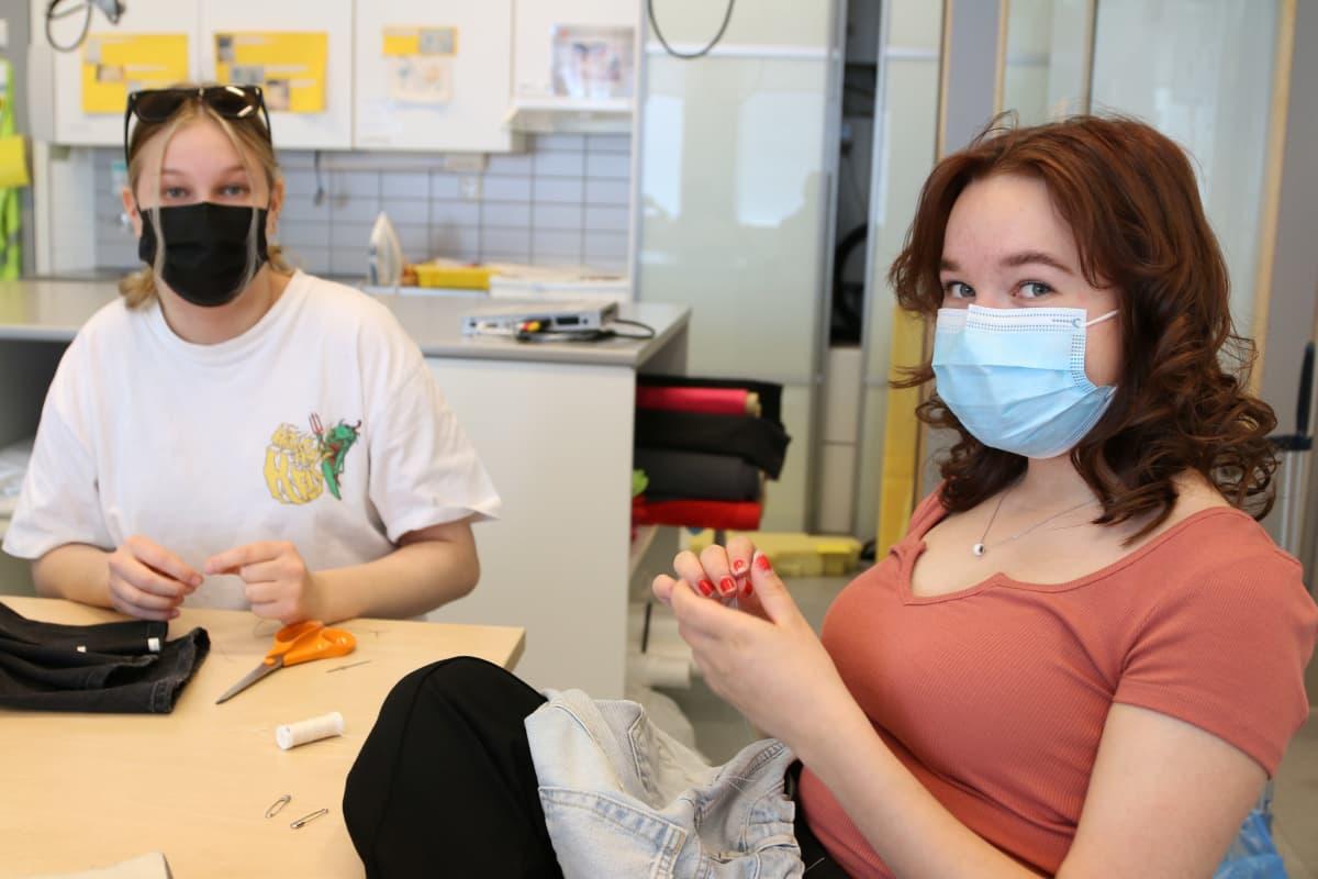 Haukiputaan lukiolaiset opettelevat työpajassa vaatteiden korjaamista.