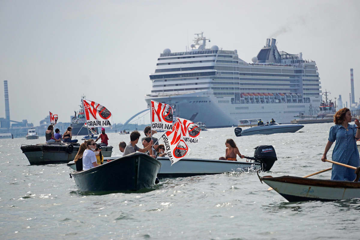 """""""Ei isoja laivoja"""" lukee mielenosoittajien kylteissä Venetsiassa."""