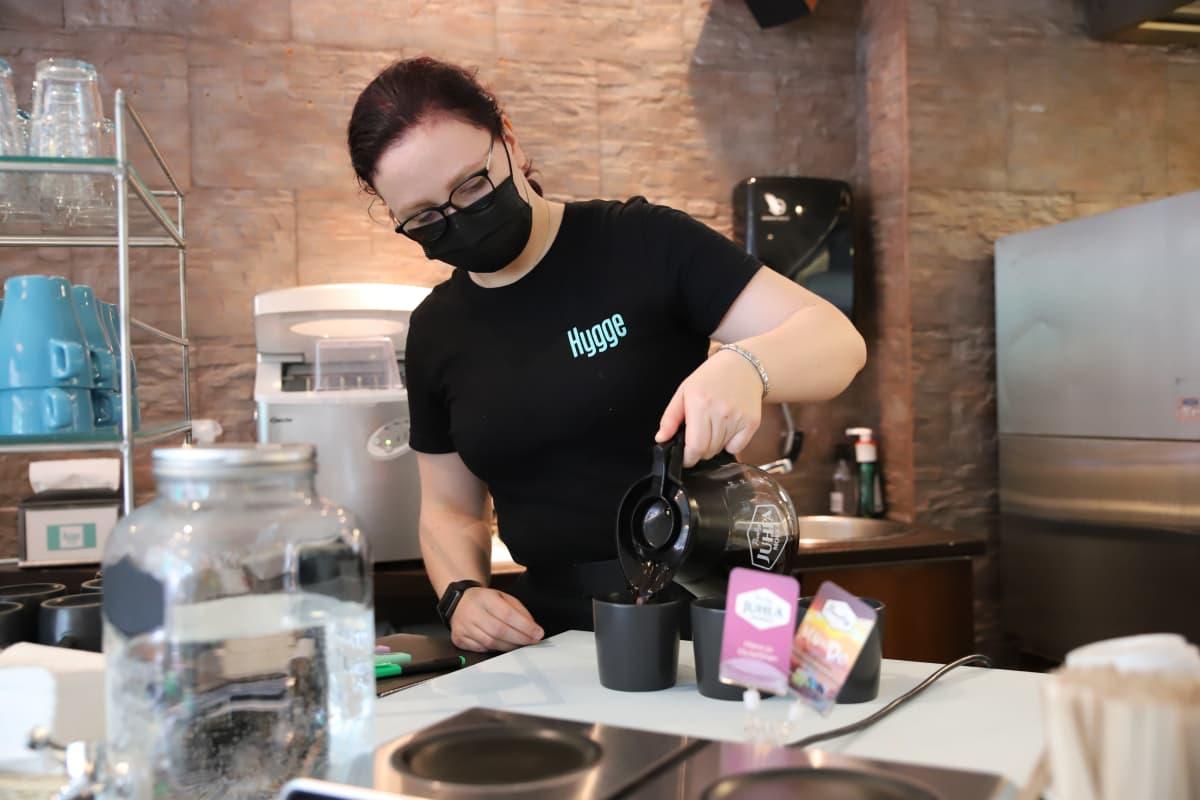 Kotkalainen Nelli Kortelainen kaatamassa kahvia Kahvila-konditoria Hyggessä.