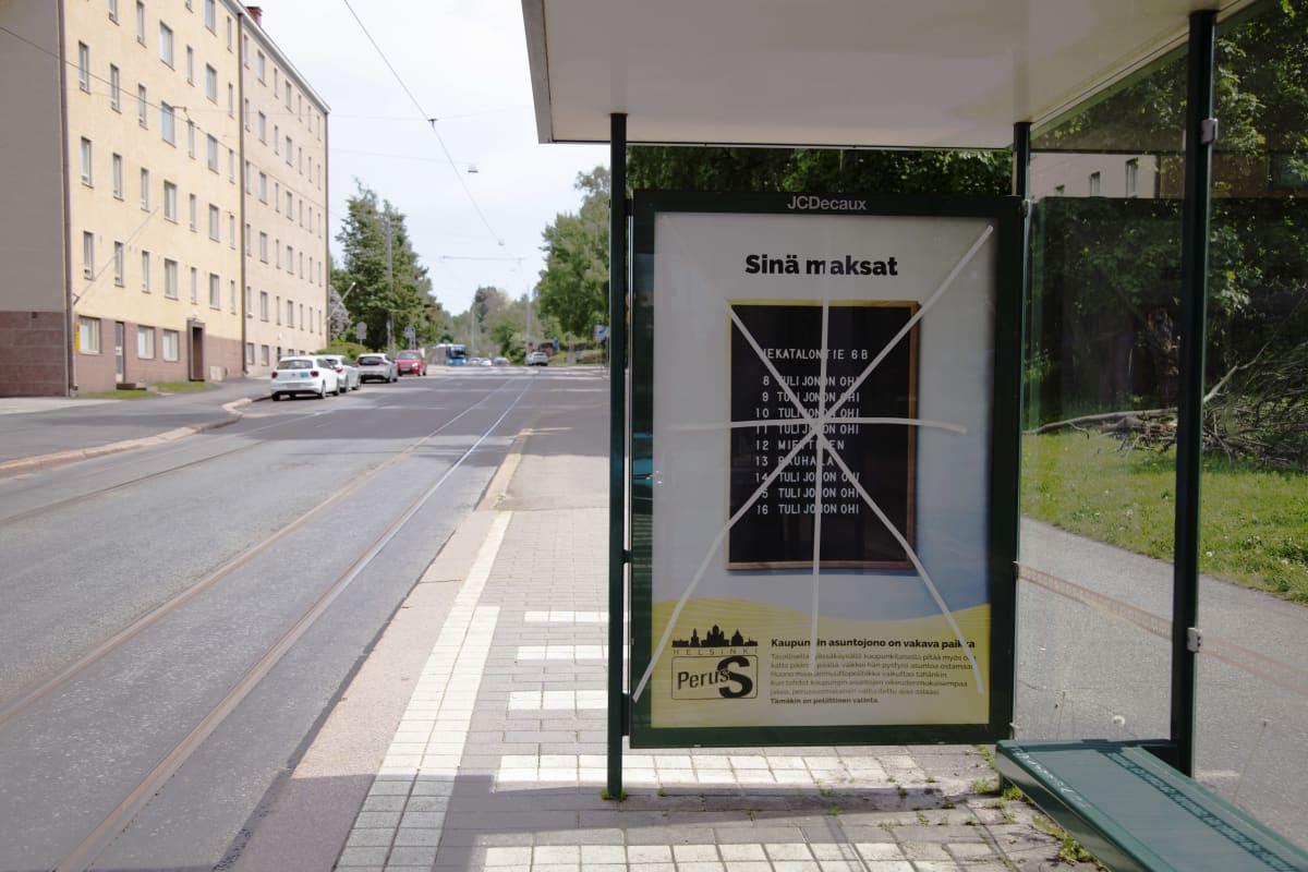Perussuomalaisten vaalimainoksen päälle on vedetty teipit Helsingin Viipurinkadulla.