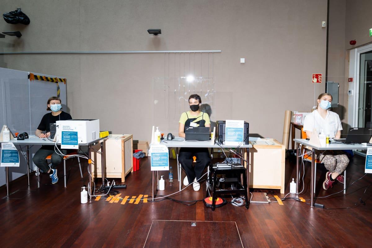 Kolme vaalityöntekijää istuu omilla äänestyspisteillään rivissä. Pöytien väleissä on vaaliuurnat, takana seinä.