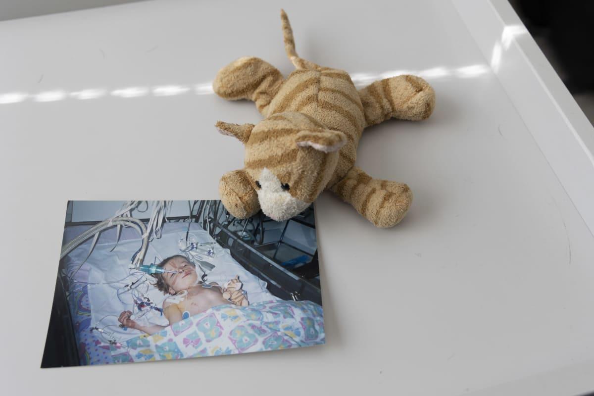 Pöydällä on valokuva Jasmin Pyyköstä sairaalassa. Valokuvan vieressä on kissapehmolelu.