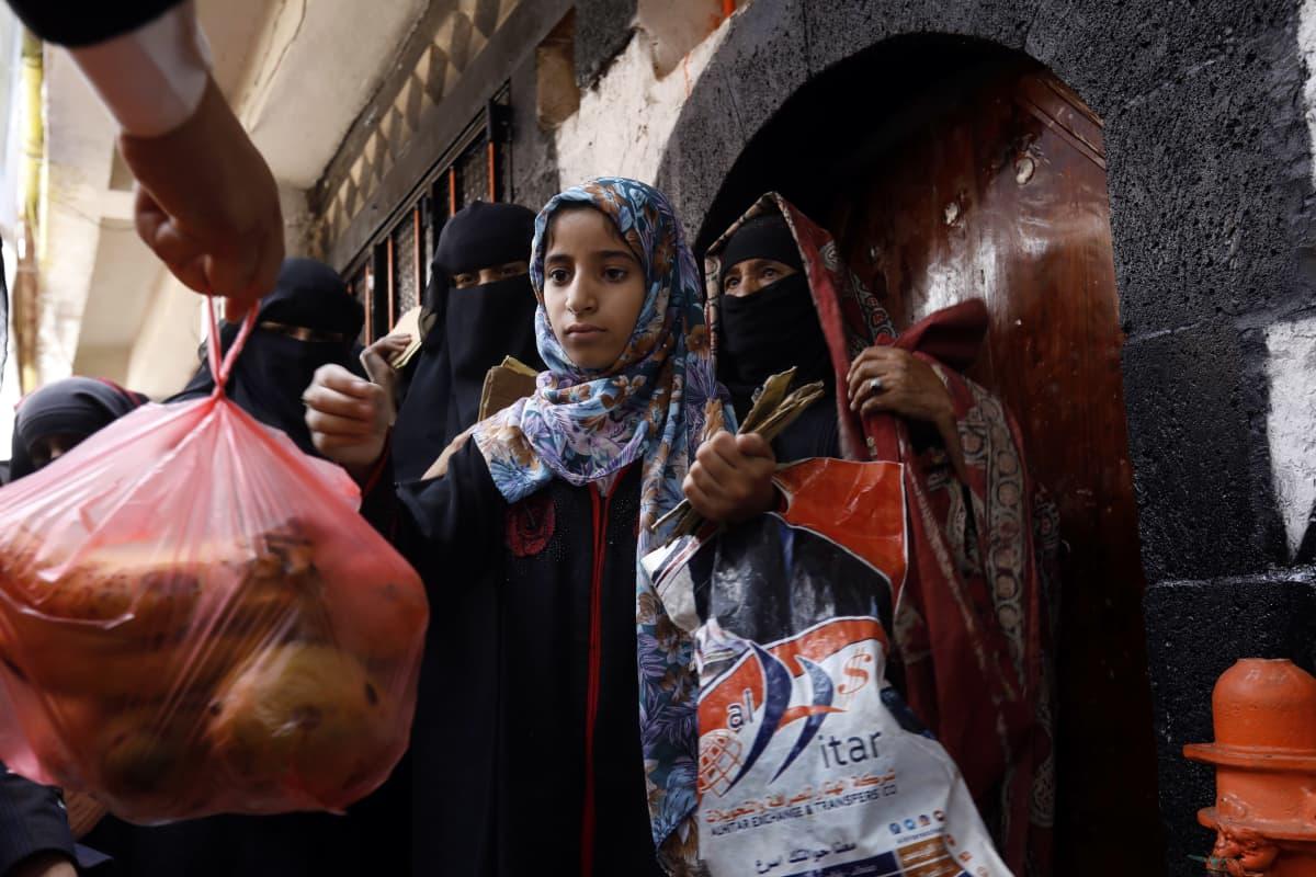 Jemeniläinen tyttö vastaanottaa ruokaa Jemenissä.