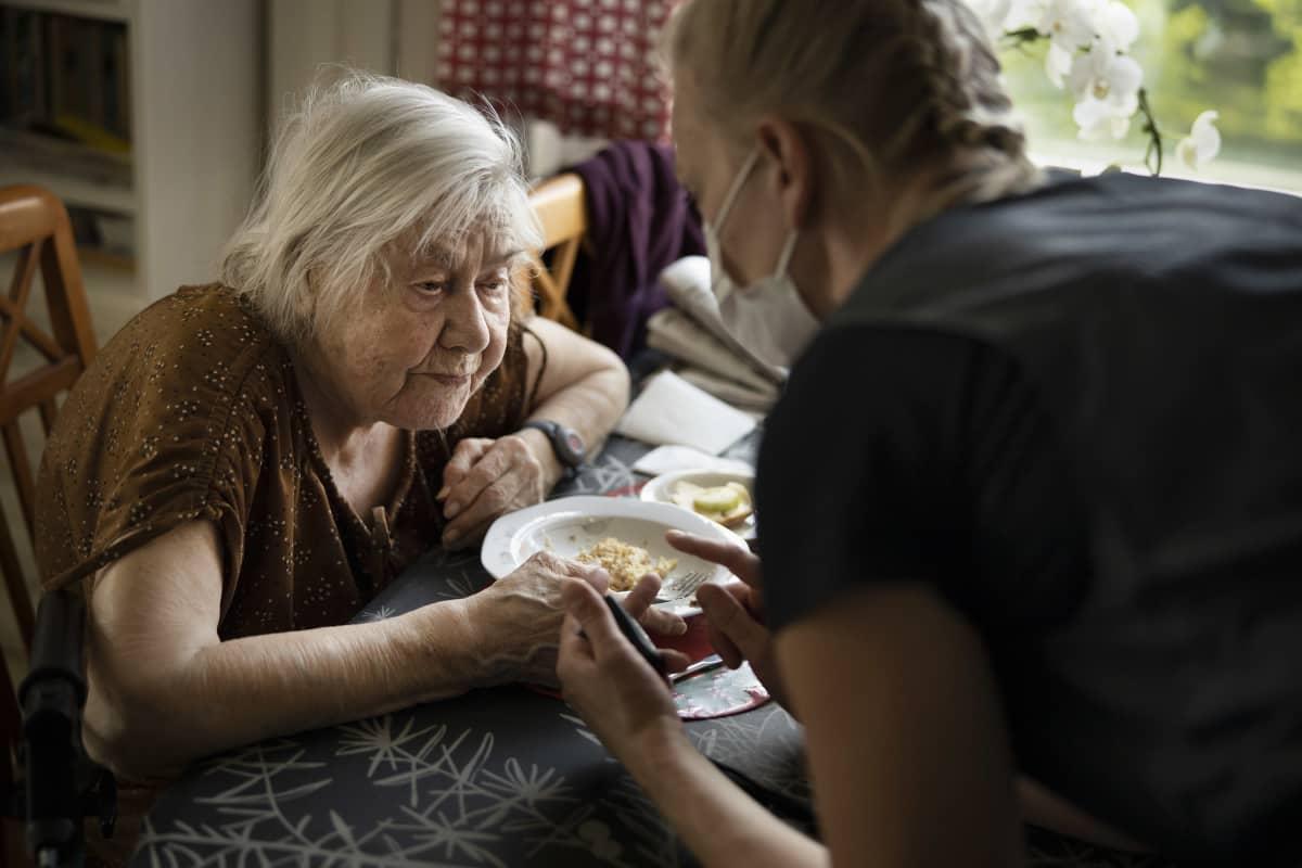 Kotihoitaja keskutelee ruokailevan vanhuksen kanssa.