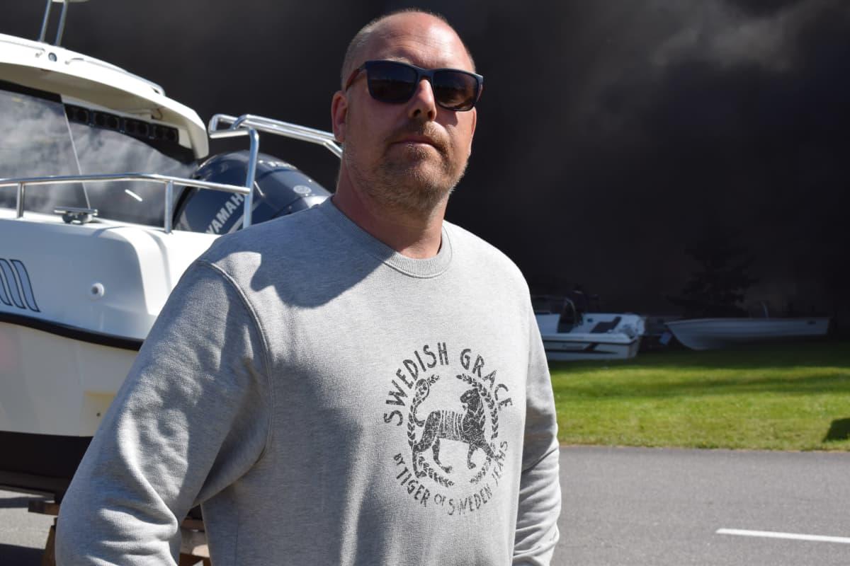En man i solglasögon och en grå collegetröja står framför en båt.