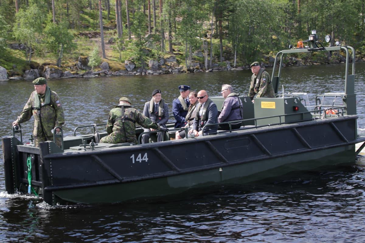 Muistotilaisuuteen osallistuneet 8 ihmistä palaavat veneellä rantaan.