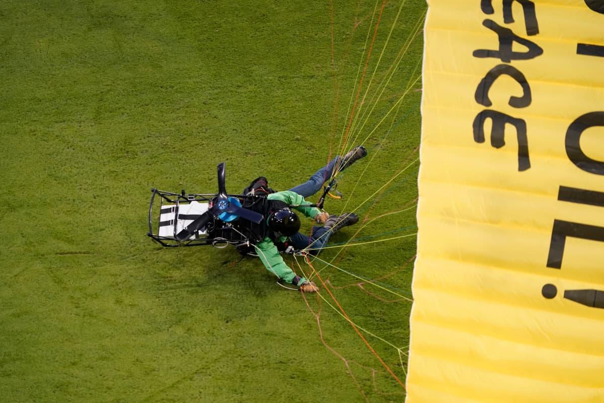 Greenpeace-aktivisti tömähtää moottoroidulla varjoliidolla maahan Münchenin Allianz-areenalla.