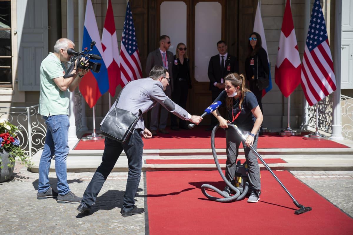 Nainen imuori punaista mattoa Villa La Grangen edustalla ennen presidentti Bidenin ja Putinin tapaamista Genevessä 16. kesäkuuta 2021.