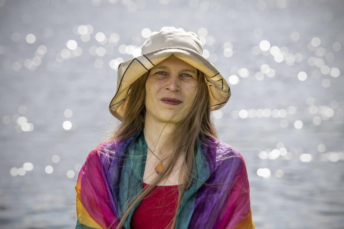 Alia Dannenberg kimaltelevan veden äärellä sateenkaarihuivi harteillaan.
