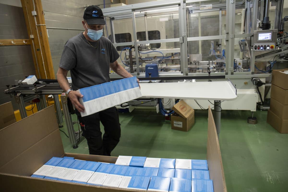 Työntekijä pakkaa kasvomaskilaatikoita suureen pahvilaatikkoon.