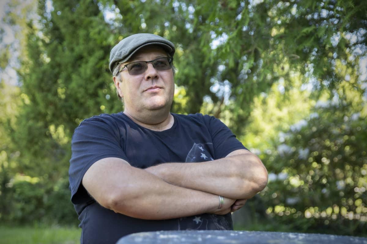 Veikko Miettinen istuu pöydän ääressä kädet puuskassa vehreässä ympäristössä.