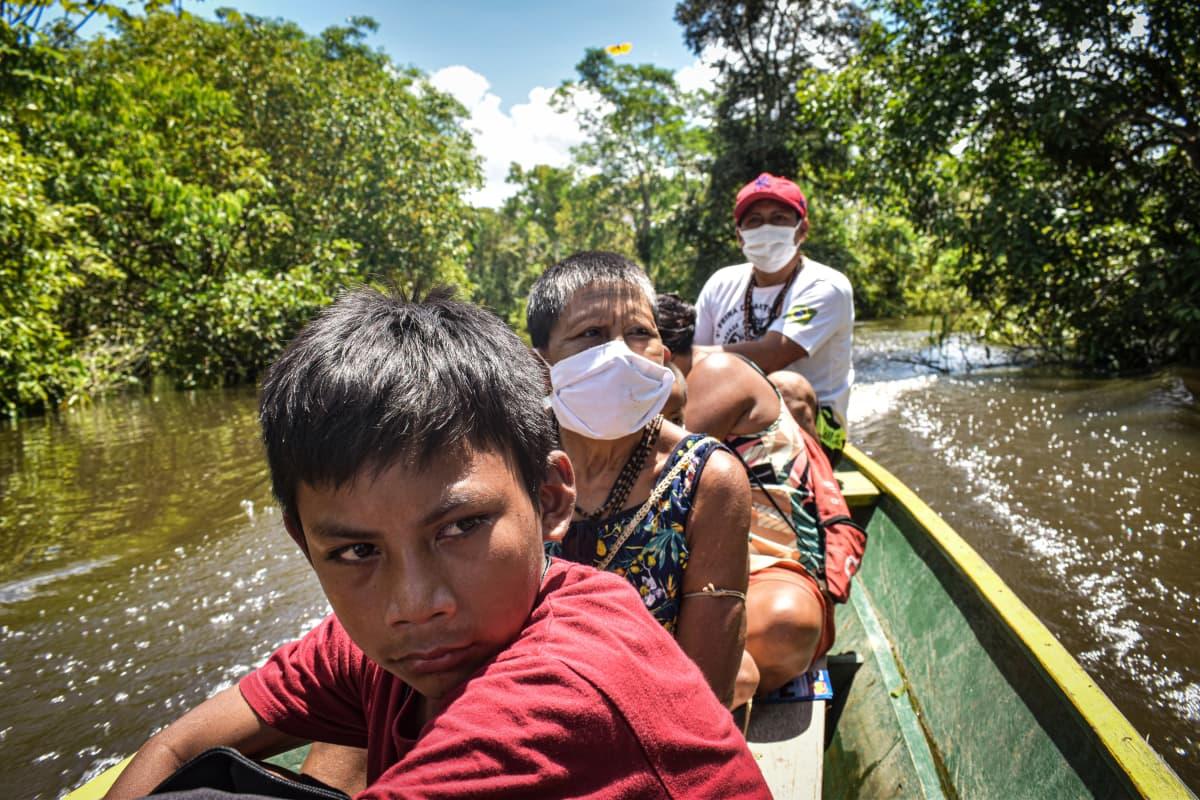 Ryhmä alkuperäiskansaan kuuluvia matkustaa veneellä.
