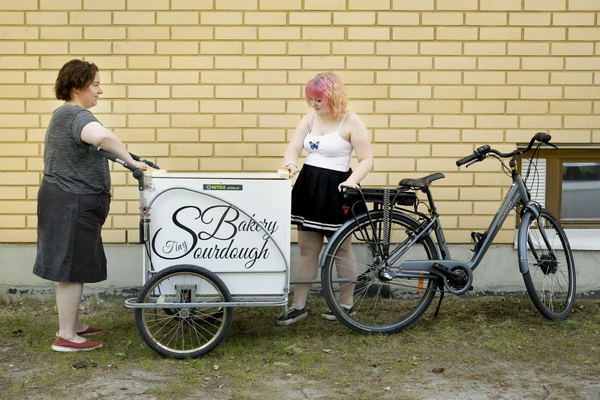 Mimmi Tick ja Vilma Hämäläinen hiovat lastipyöränsä lastilaatikkoa hiomapaperilla.