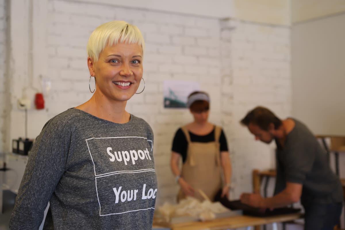 Vaalea nainen hymyilee kameralle, taustalla kaksi ihmistä lajittelee hiuskuituja pöydän ääressä